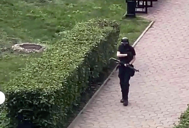 Тимур Бекмансуров с ружьем идет ко входу Пермского госуниверситета