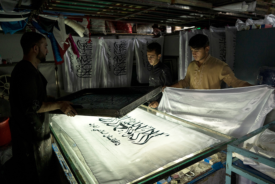 Workers hand print Taliban flags in a small workshop in Kabul's Jawid market, Afghanistan, Sunday, Sept. 12, 2021. The flag shop, tucked away in the courtyard of a Kabul market, has documented Afghanistan's turbulent history over the decades with its ever-changing merchandise. Now the shop is filled with white Taliban flags, emblazoned with the Quran's Muslim statement of faith, in black Arabic lettering.