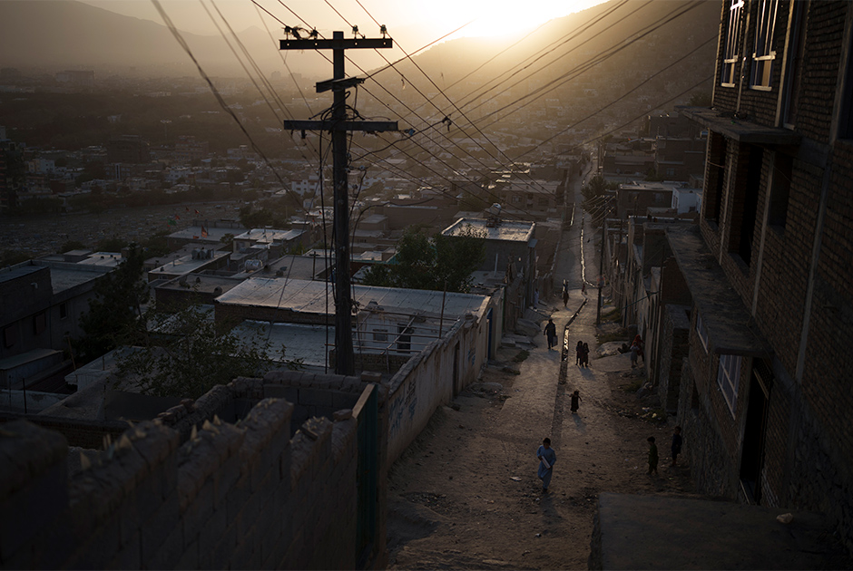 People walk through an alleyway as the sun sets in Kabul, Afghanistan, Thursday, Sept. 16, 2021.