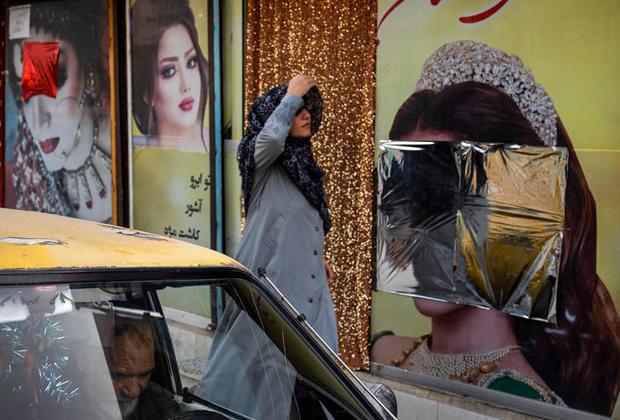 Женщина проходит мимо салона красоты в Кабуле