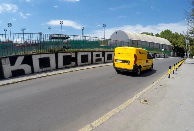 Автомобиль проезжает мимо граффити: «Косово — святая земля Сербии» в Белграде, Сербия