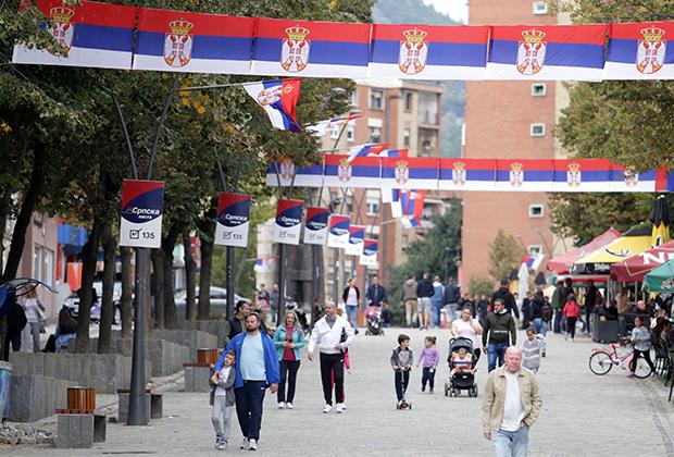 Люди идут по улице, украшенной сербскими флагами, в Косовска-Митровице