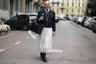 Один из гостей Недели моды размыл границы гендера, соединив в своем образе элементы мужского и женского гардероба. На нем — темный бомбер, белая рубашка, черный галстук, полупрозрачная кружевная юбка длины макси и лакированные туфли на каблуках с открытым носом. В качестве аксессуаров мужчина выбрал черную кожаную сумку Prada, солнцезащитные очки и крупное кольцо с драгоценным камнем.