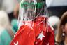 Один из посетителей Недели моды в Париже привлек внимание фотографов своим эпатажным образом. Темнокожего мужчину засняли в ярко-красной лакированной куртке с аппликациями в виде белых звезд на спине и рукавах. Помимо этого, он надел на голову маску из прозрачного пластика с бахромой и солнцезащитные очки в неоновой зеленой оправе.